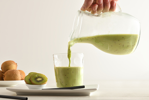 Person serving kiwi drink from jug with cut fruit in containers on kitchen bench isolated white. Front view.