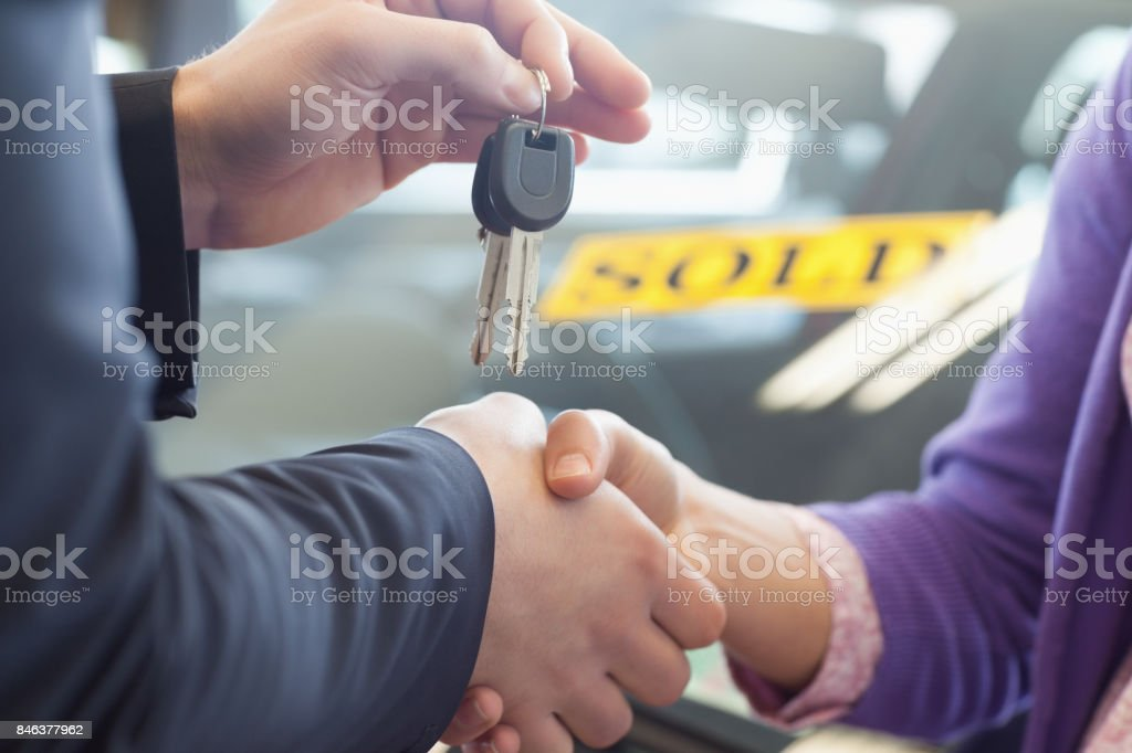 Person shaking hands in front of a sold car stock photo