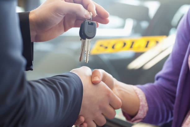person shaking hands in front of a sold car - used car selling stock pictures, royalty-free photos & images