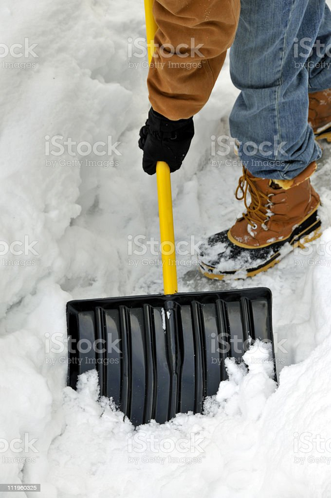 A person shoveling a path in winter royalty-free stock photo