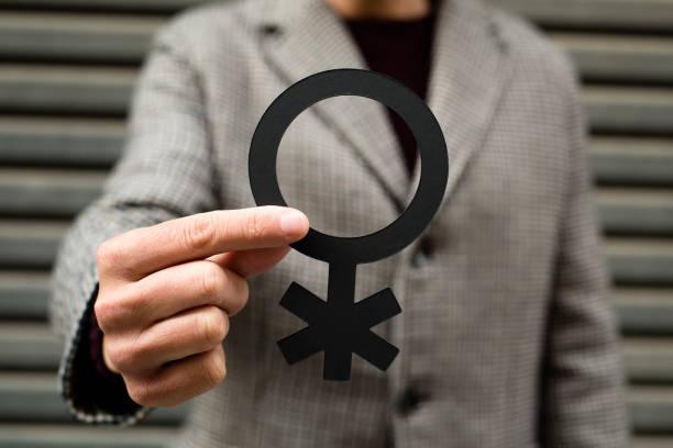 """非バイナリ性別シンボルを示す人 - """"gender fluid"""" ストックフォトと画像"""