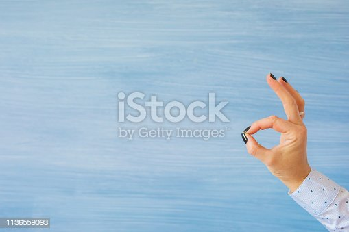 Female's hand showing ok gesture on empty blue background