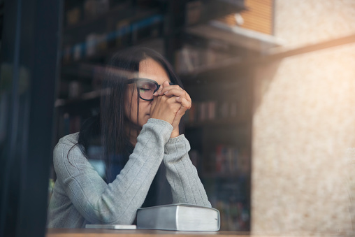 Person side view, Asian Women sad, broken heart and depressed about a bad relationship.Young thoughtful girl sitting alone and negative thinking in a coffee shop.Depressed and thoughtful concept.