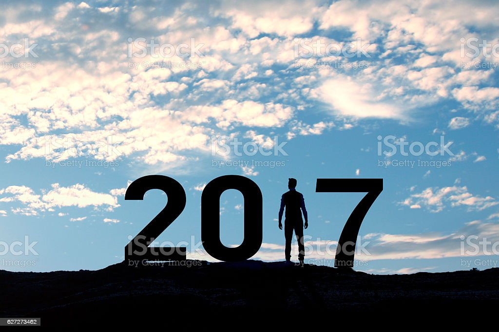 Person silhouette standing in 2017 on the hill at sunset stock photo