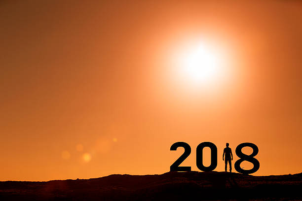 Person silhouette standing in 2018 on the hill at sunset stock photo