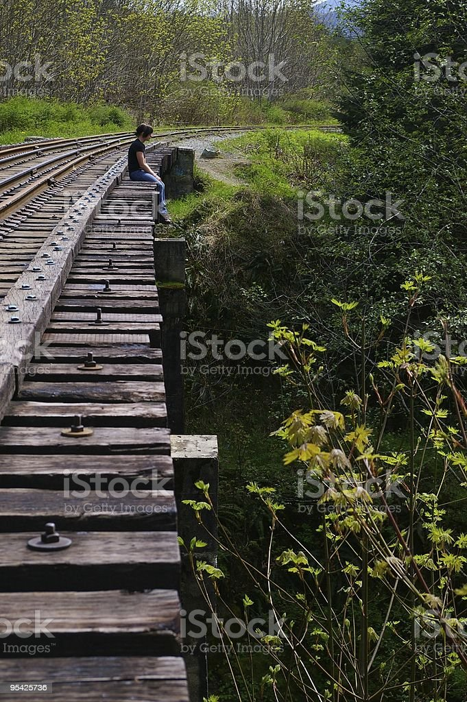 Person sitting alone in a railway stock photo