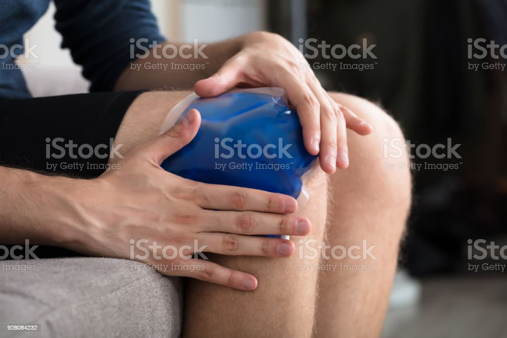 Person Sitting And Applying Ice Gel Pack On Knee stock photo
