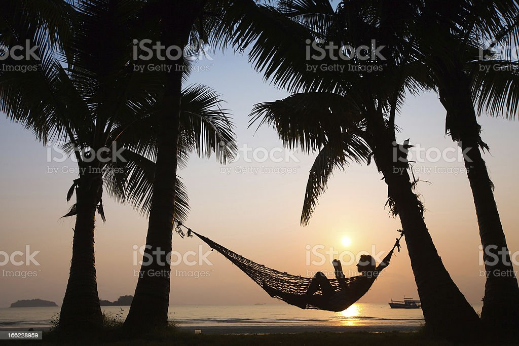 A person sitting in a hammock on the beach at sunset royalty-free stock photo