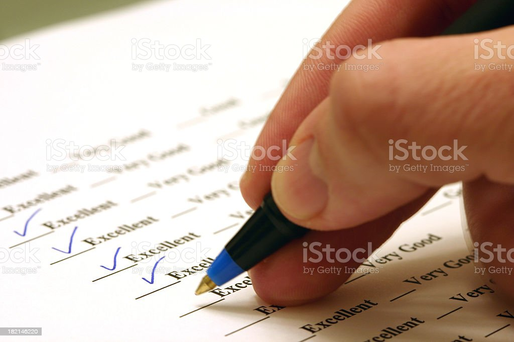 Person sitting in a survey ticking excellent royalty-free stock photo
