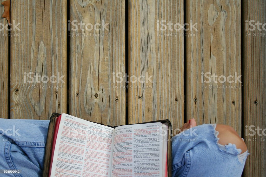 Person sitting on wood deck reading Bible stock photo