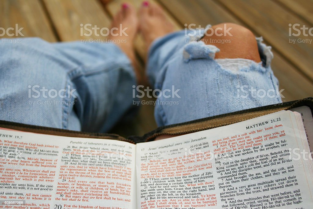 Person sitting on wooden deck reading Bible stock photo
