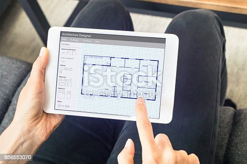 istock Person sketching home design architecture project on digital tablet, blueprint 856553070