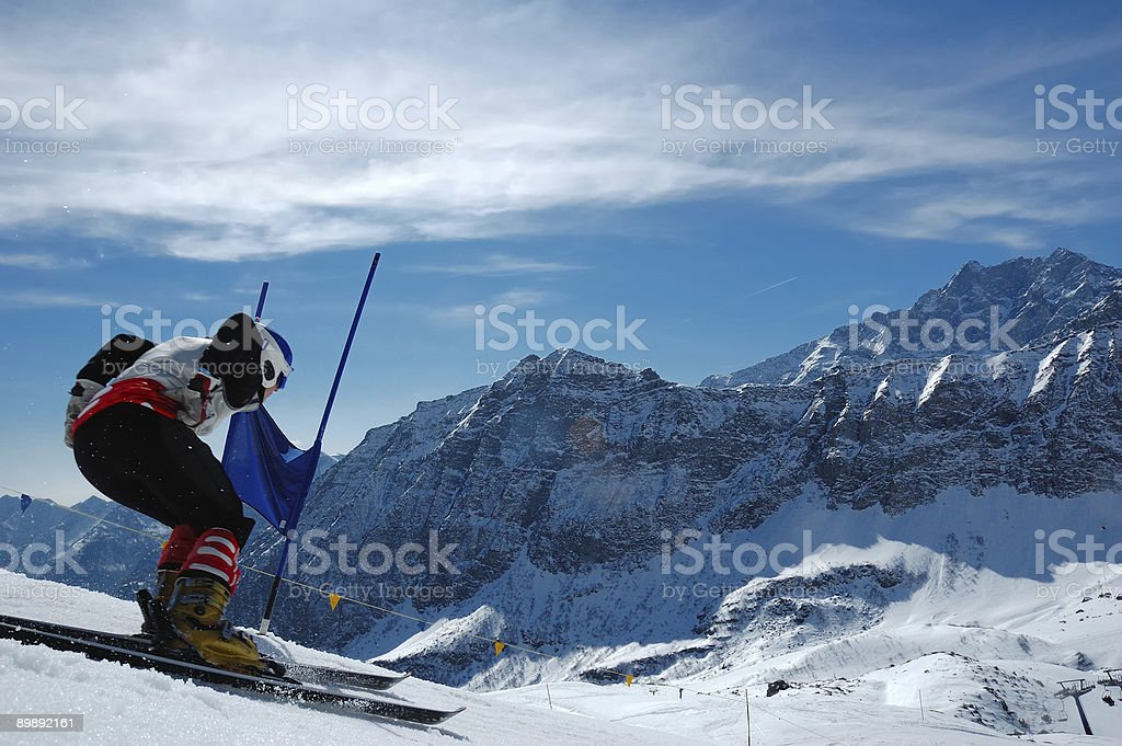 A person skiing down a hill in the wintertime stock photo