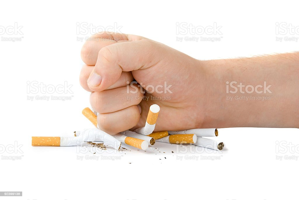 Person smashing cigarettes to stop smoking stock photo