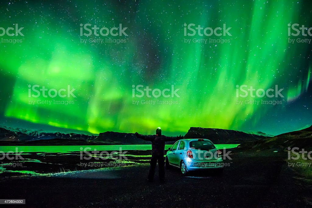 Person spreading arms under celestial lights Aurora Borealis above Iceland - Royaltyfri 20-24 år Bildbanksbilder