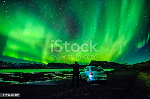 istock Person spreading arms under celestial lights Aurora Borealis above Iceland 472634332