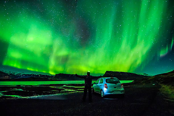 person spreading arms under celestial lights aurora borealis above iceland - nightsky bildbanksfoton och bilder
