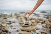 Detail of person stacking rocks by the sea. Cloudy day, Australia.