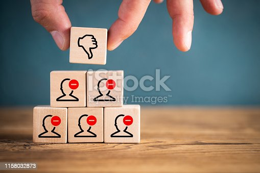 istock Person stacking toy blocks with thumbs down 1158032873