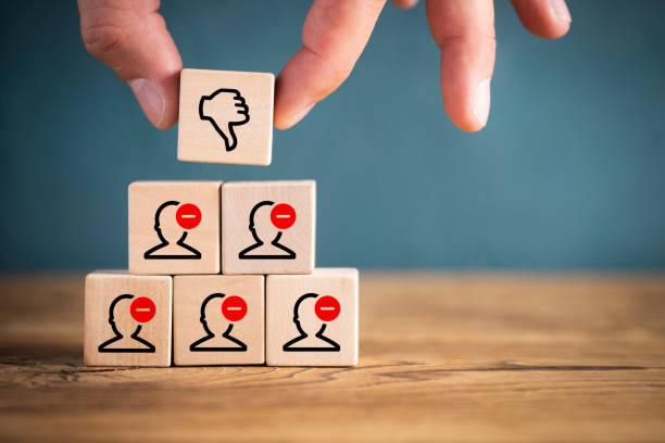 Person stacking toy blocks with thumbs down Person stacking toy blocks with thumbs down icon on a pyramid of blocks showing human heads with negative minus signs in a conceptual image of failure and rejection minus sign stock pictures, royalty-free photos & images