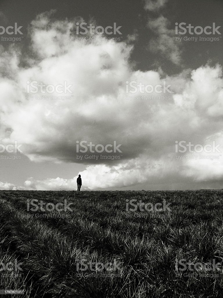 Person Standing Alone in a Dark Field royalty-free stock photo