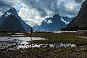 Silhouette of unrecognizable person standing in middle of wet valley on background of magnificent mountains and overcast sky