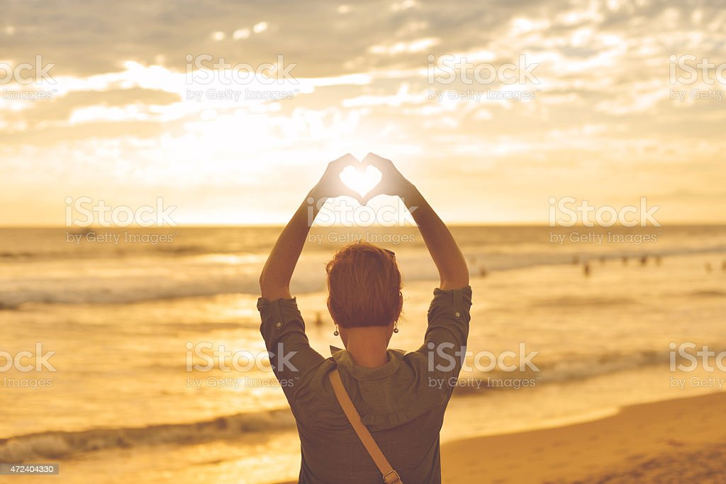 A person standing on a beach making a heart with their hands stock photo