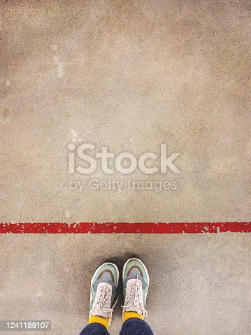 Person standing on red line - social distancing sing as a new normal life trend. Back to normal and keep distance concept. New after quarantine and isolation rules in public places