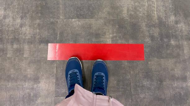 uma pessoa parada no chão com uma linha vermelha. conceito de manter distância, distanciamento social, quarentena ou isolamento - distante - fotografias e filmes do acervo