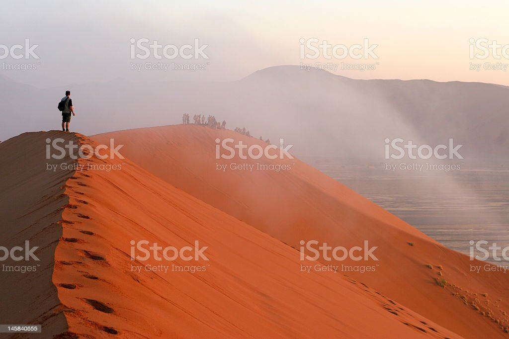Person standing on top of a red sand desert hill royalty-free stock photo