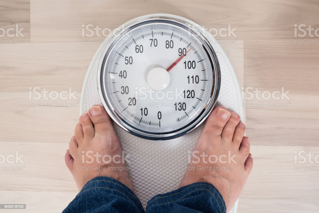 Person Standing On Weighing Scale stock photo