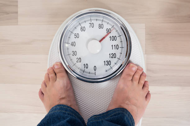 person standing on weighing scale - old man feet stock photos and pictures