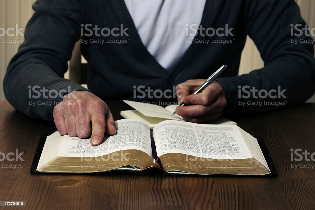 Person studying the Bible with pen and notebook royalty-free stock photo