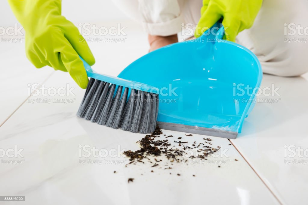 Person Sweeping Floor With Broom And Dustpan stock photo