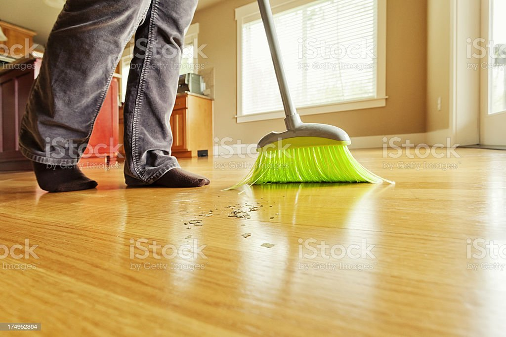 Person Sweeping Mess on Hardwood Floor with Broom stock photo