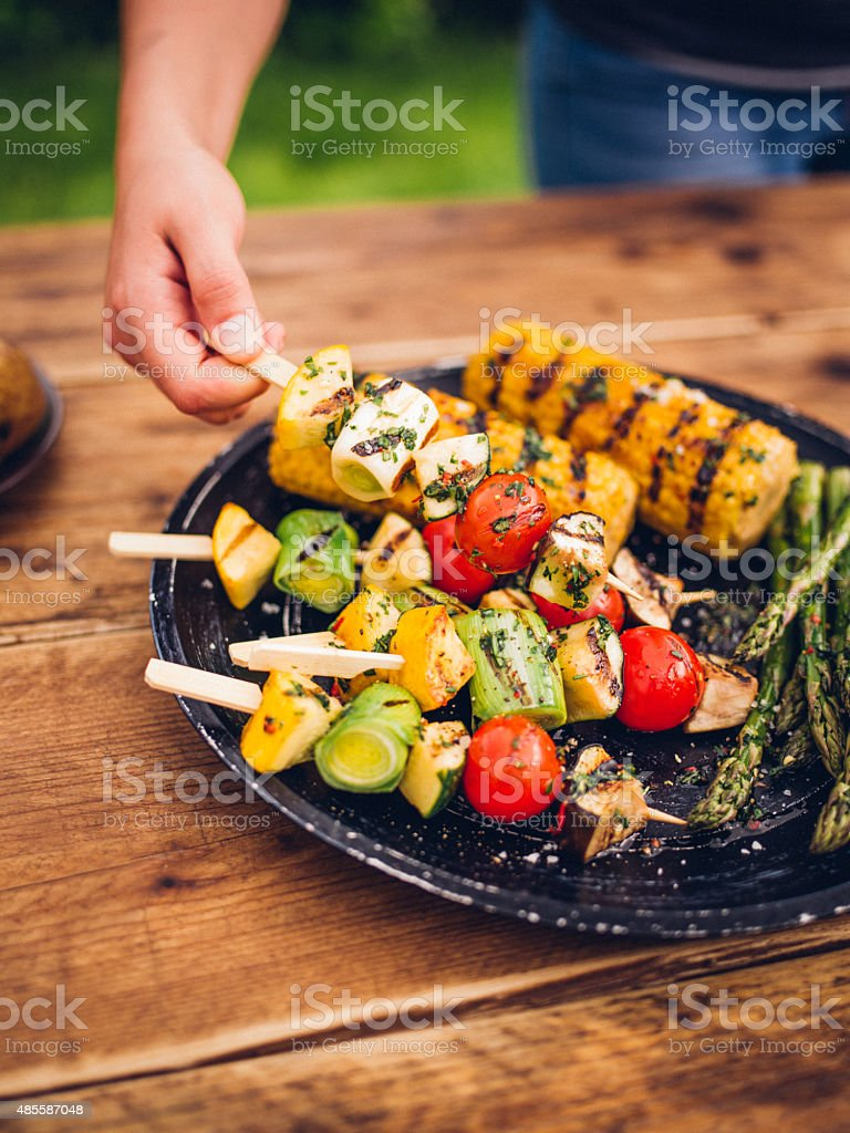 Person taking a delicious grilled vegetable kebab from plate outdoors stock photo
