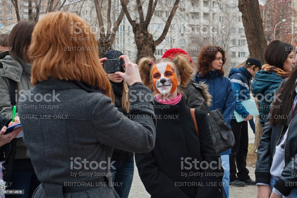 Person taking a picture of girl in makeup in international action for the protection of animals