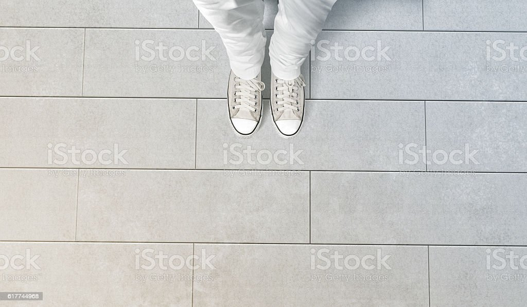 Person taking photo of his feet stand on concrete floor stock photo