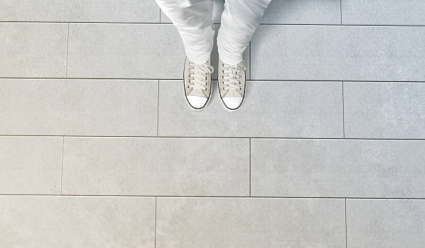 Person taking photo of his feet stand on concrete floor Person taking photo of his feet stand on concrete floor, isolated, top view, clipping path. Ground design mock up. Man wear gumshoes and watching down. Deck flooring mockup template. single step stock pictures, royalty-free photos & images