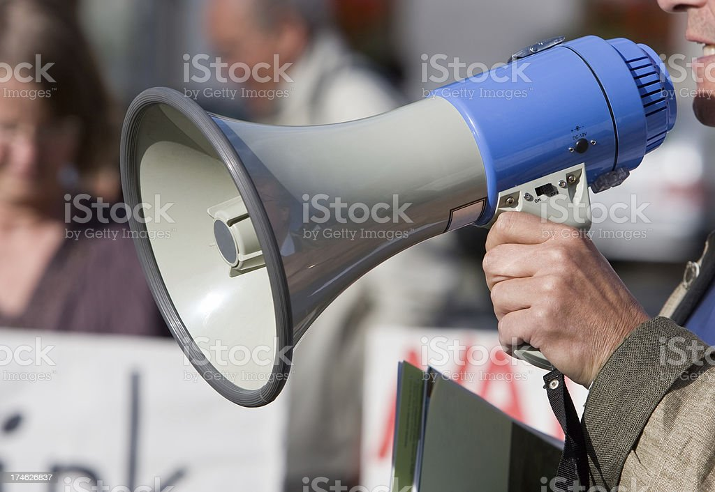 Person talking in a blow horn at a demonstration stock photo