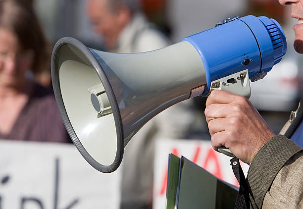 Person talking in a blow horn at a demonstration Close up of a megaphone during a demonstration. RAW-file developed with Adobe Lightroom. labor union stock pictures, royalty-free photos & images