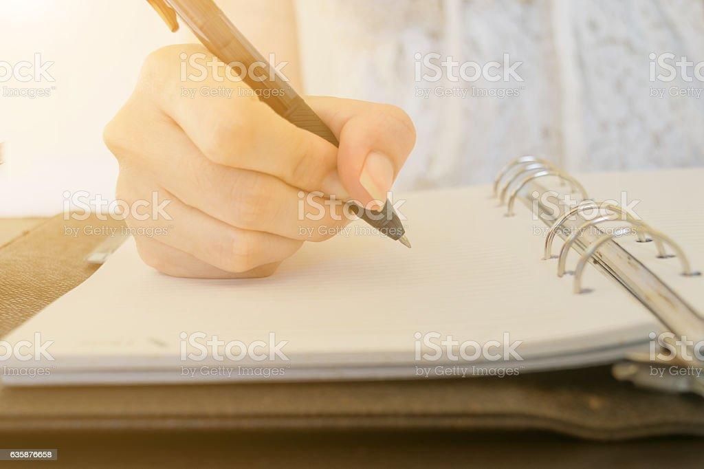 person the pen writing on desks stock photo