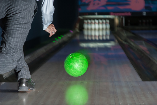 Person throwing a green bowling ball.