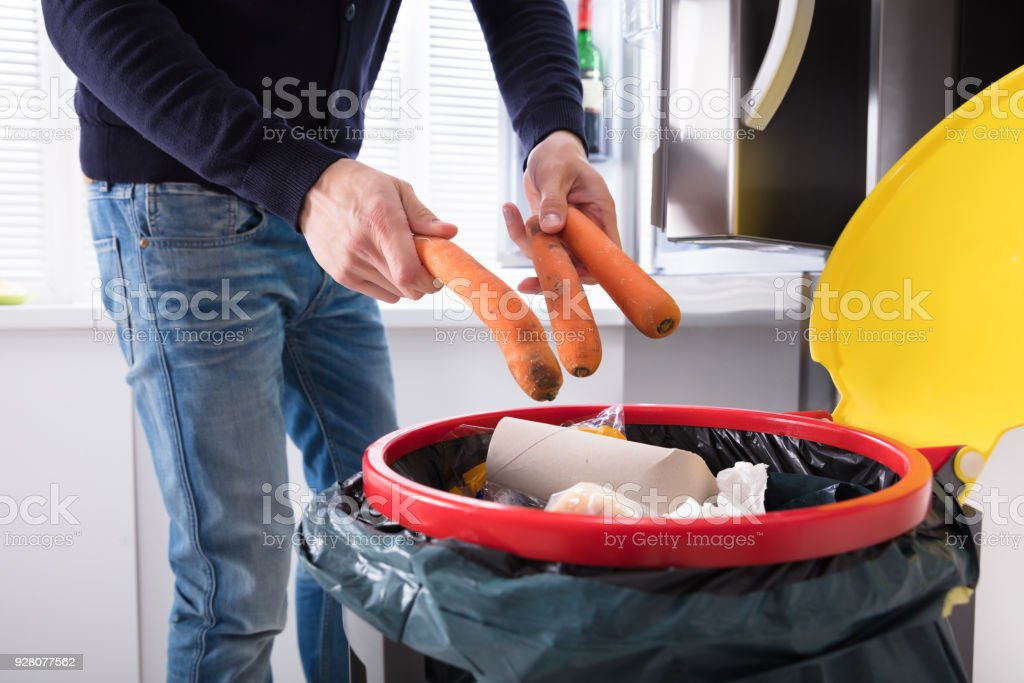 Person Throwing Carrot In Dustbin royalty-free stock photo