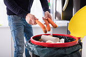 istock Person Throwing Carrot In Dustbin 928077562
