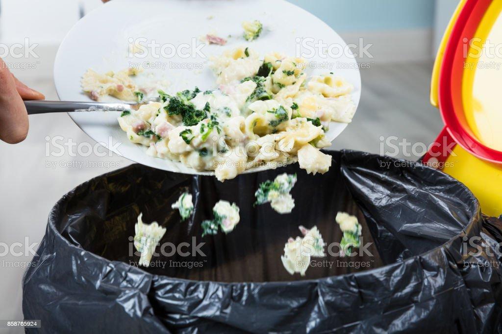 Person kastar kokt Pasta i papperskorgen bildbanksfoto