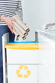 Close-up of person throwing rolls of paper to white bin with yellow symbol for sorted waste