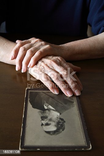 478384809 istock photo A person touching and viewing an old man portrait on a table 183281108