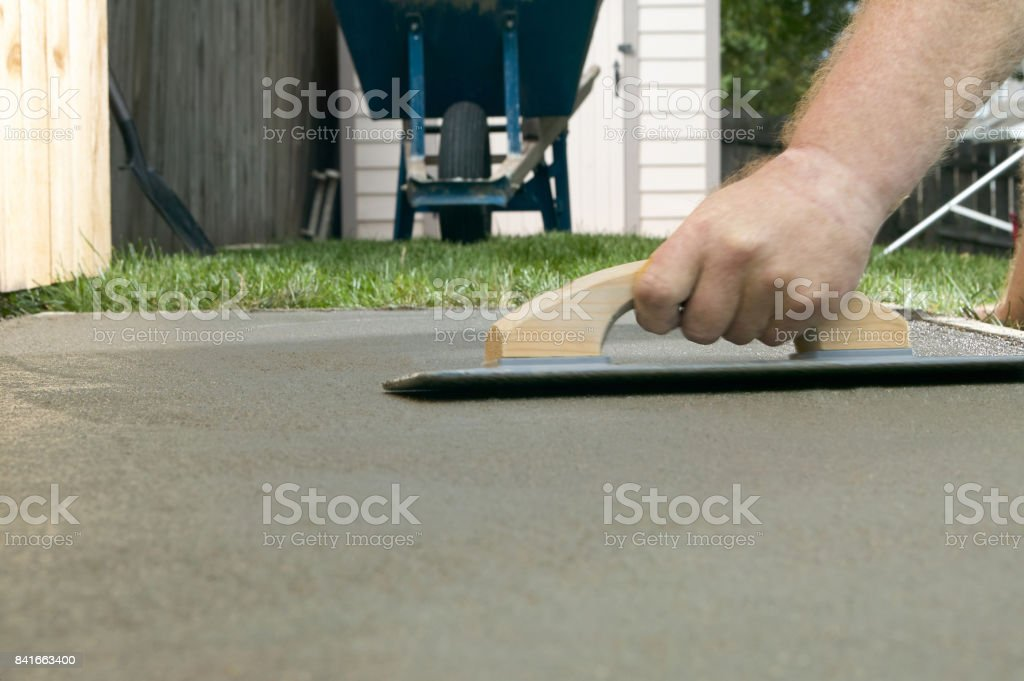 Person troweling wet cement with concrete screed stock photo