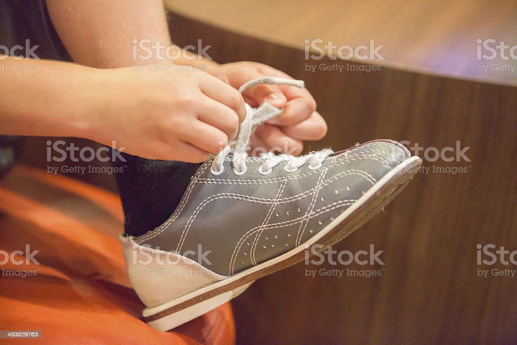 A person tying a gray bowling show stock photo